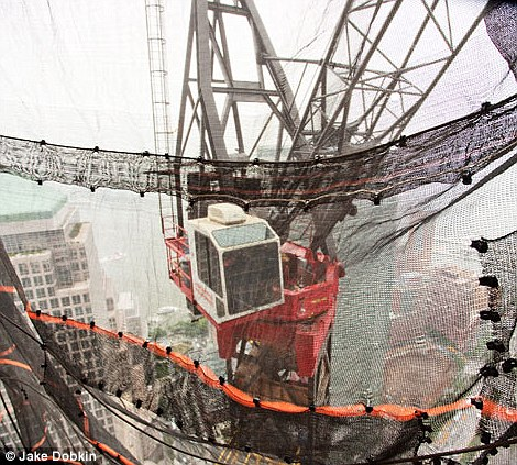 New heights: Left, a construction worker on the 61st floor of One World Trade Center, where glass has yet to be placed. Right, a crane operator hovers in a glass-bottomed booth