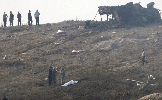 Catastrophe: Covered bodies lie at the scene while emergency personnel view the scene at military base in southern Cyprus
