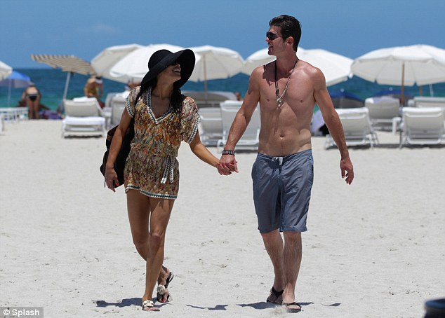 Holiday romance: Paula and Robin hold hands as they leave the beach