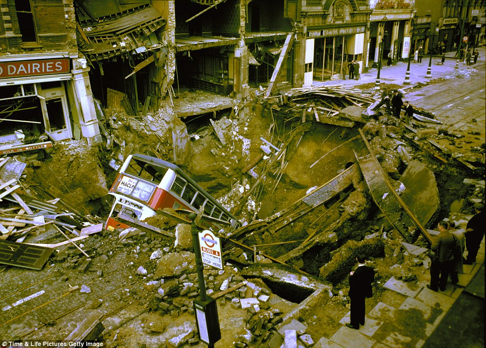 High-street terror: The incredible destruction of the Blitz is revealed in this image as a double decker bus is plunged into a bombed crater
