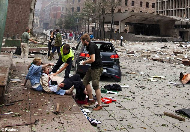 An injured man is helped in the immediate aftermath of the powerful explosion that tore apart the government district of Oslo yesterday