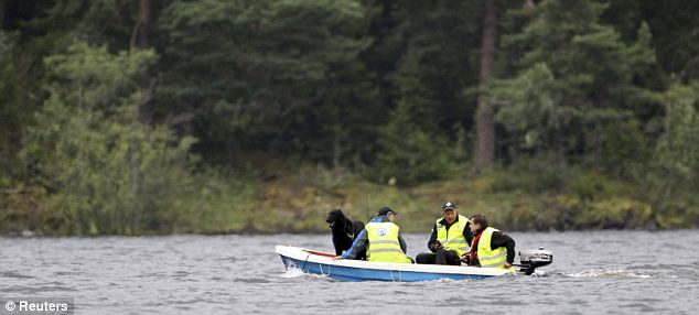 Rescue workers with a sniffer dog search for bodies along the shore of Utoya island. A 32-year-old man has been charged with terrorism offences