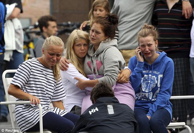 Their faces stricken with grief, these teenagers react as Norway's King Harald and Queen Sonja arrive to comfort them outside a hotel where survivors and family members are staying