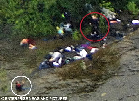 Horror: This picture shows Breivik stalking Utoya island, surrounded by the bodies of his young victims, with one in the water pleading for his life