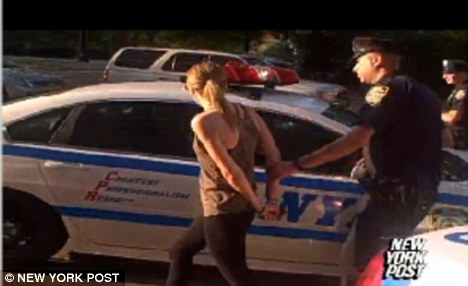 Cuffed: Police officers lead Jennifer Tzar away from her apartment and off to the police station