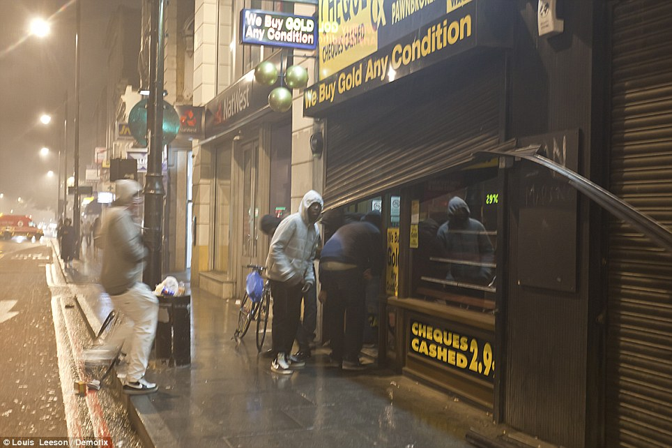 Brixton: A pawnbroker is hit by a gang of hooded thieves as a photographer watches on