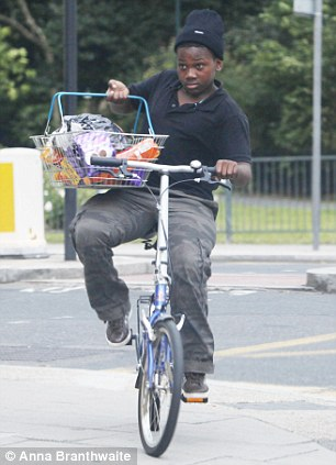 Snacks: A youngster on his bike carries in a basket groceries suspected of coming from a looted Tesco