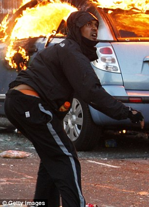 A rioter throws ab object in front of a burning car