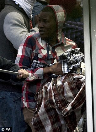 A looter holds a haul of check shirts to match the one he's already wearing