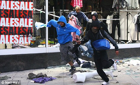 Making a run for it: These four looters dash from the Blue Inc store in Peckham with looted goods