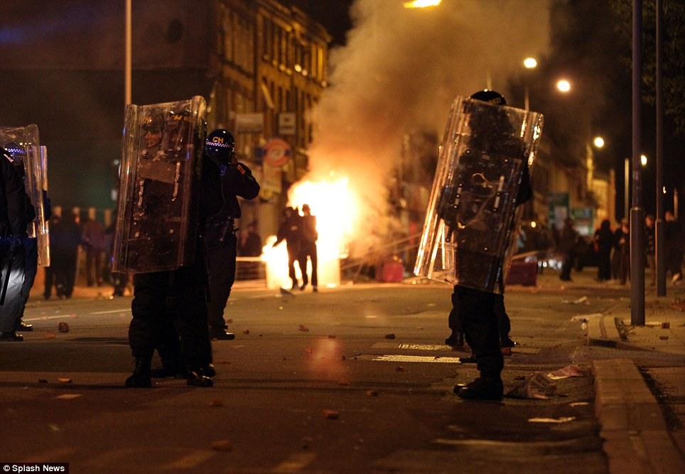 On guard: Riot police stand with shields in front of a street fire in the Toxteth area of Liverpool last night which was hit by riots