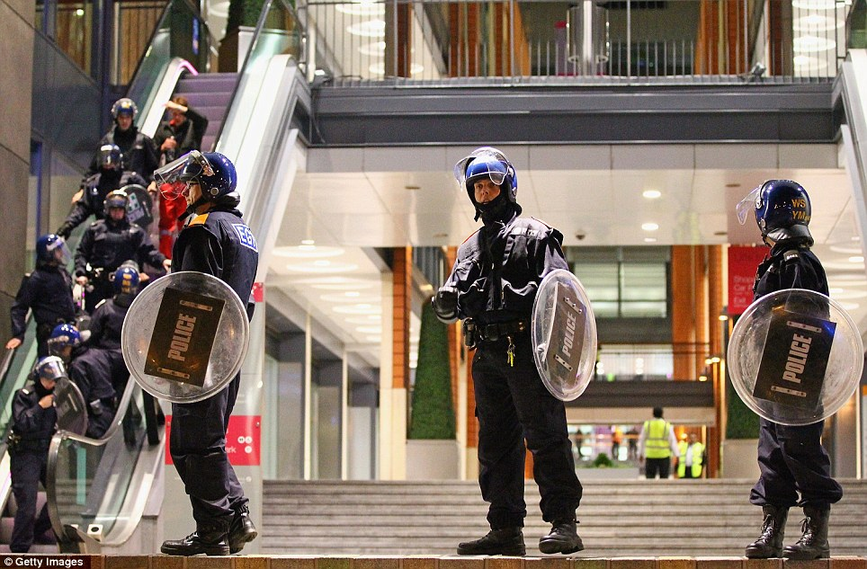 Reinforcements: Police file down the escalator and stand guard at the Mailbox shopping and hotel complex in Birmingham City Centre yesterday