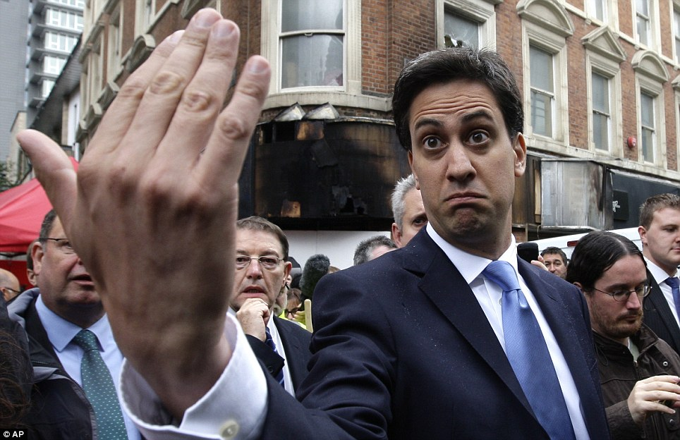 Walkabout: Labour leader Ed Miliband is heckled and called 'Dave' as he stands outside a burnt-out Miss Selfridge shop on Market Street in Manchester after rioting in the city
