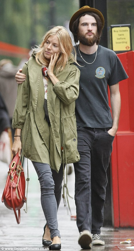 Smitten: Sienna Miller and her boyfriend were dressed down after enjoying a lunch in London - with Tom Sturridge sported a huge beard