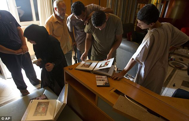 Snap happy: Rebel fighters and civilians browse through Gaddafi's photo albums