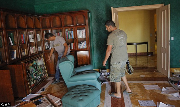 Looting: A pair of rebels go through the book cases of Aisha Gaddafi at her home in Tripoli