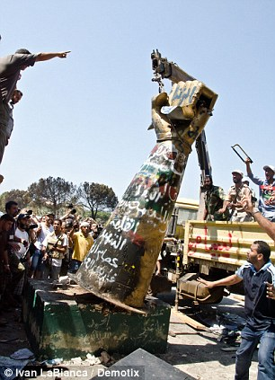 Rebels remove the 'Fist crushing a US fighter jet' sculpture with a crane at Gaddafi's Bab al-Aziziya compound