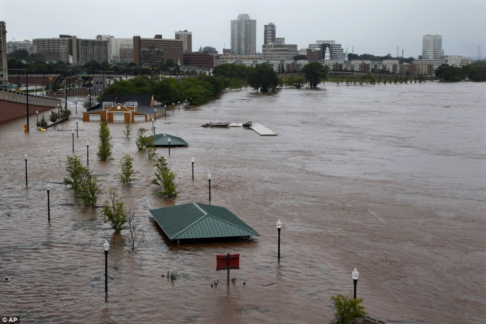 Underwater: Downtown New Brunswick, New Jersey, can be see near the overflowing Raritan River on Sunday as heavy rains left by Hurricane Irene are causing inland flooding of rivers and streams