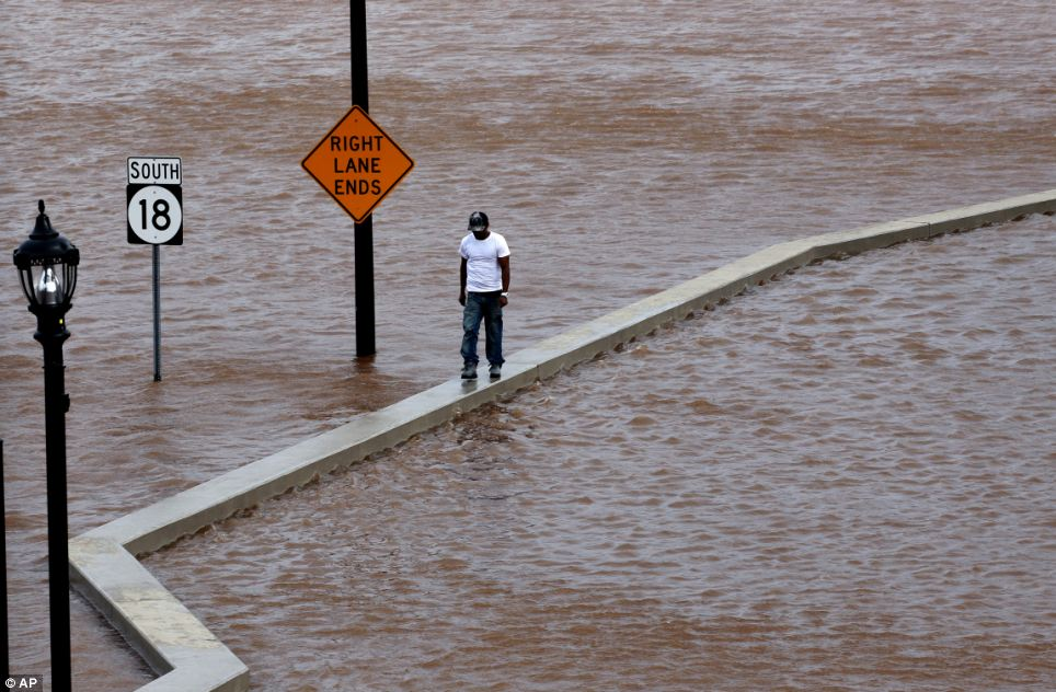 Flooded roads: A man walks on top of a wall next to a flooded highway in New Brunswick, New Jersey, as heavy rains left by Hurricane Irene are causing inland flooding of rivers and streams