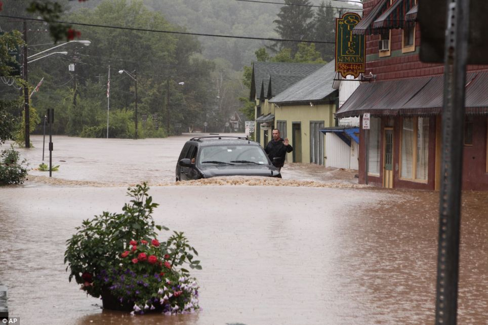Flooding: A security guard hangs on the door of governor Andrew Cuomo's SUV in the middle of a flooded street in Margaretville, New York on Sunday