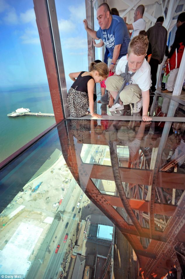 Vertical drop: The Hill family from Blackpool look down through the glass floor