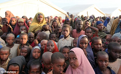 Aid: Famine-stricken displaced people, many of them children, wait to receive food from members of al Shabaab, the Al Qaeda-linked Somali insurgents, at a camp nea rthe capital