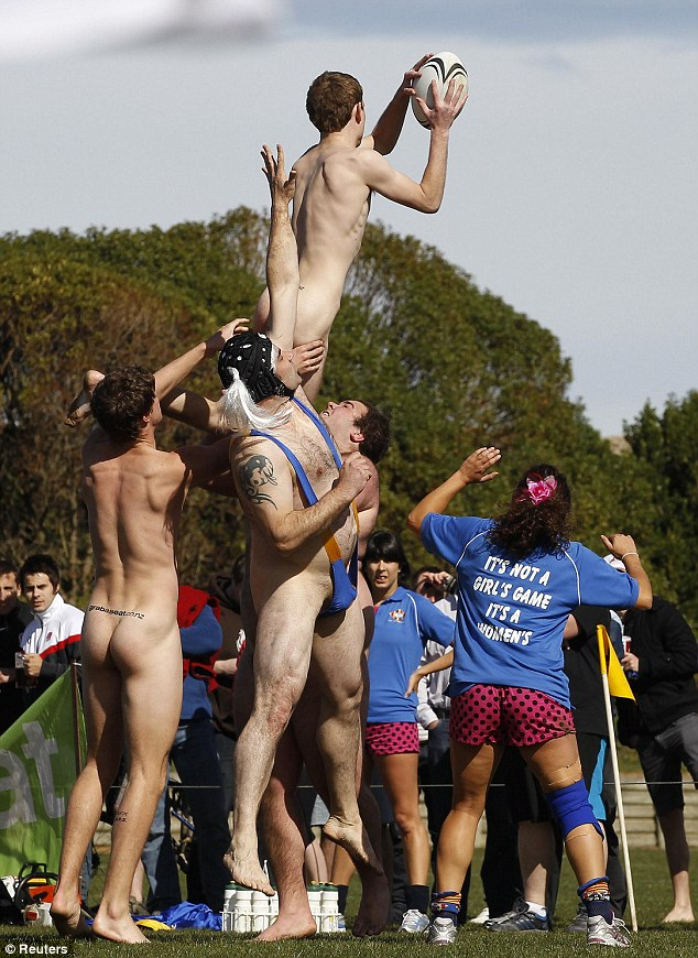 A naked rugby player from the Nude Blacks catches the ball during a line-out in their match against the Spanish team Las Conquistadoras