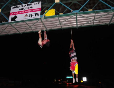 Brutal: The disemboweled corpses of a man (right) and a woman hang from a pedestrian bridge in Nuevo Laredo after they were murdered by a drugs cartel.