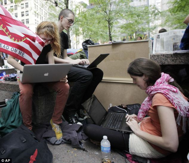 Tools of capitalism: Protesters in Zucotti Park, New York, have taken to the internet and social networking sites to promote their cause and give live feeds