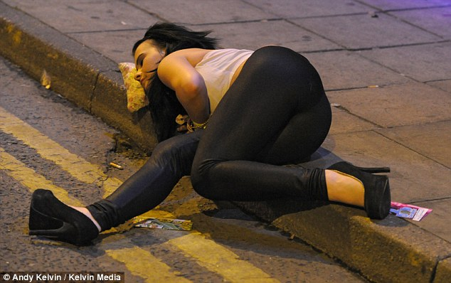 Out for the night: A 'tired' young woman uses her handbag as a makeshift pillow after hours of cut-price drinking at The Show Bar in Warrington, Cheshire