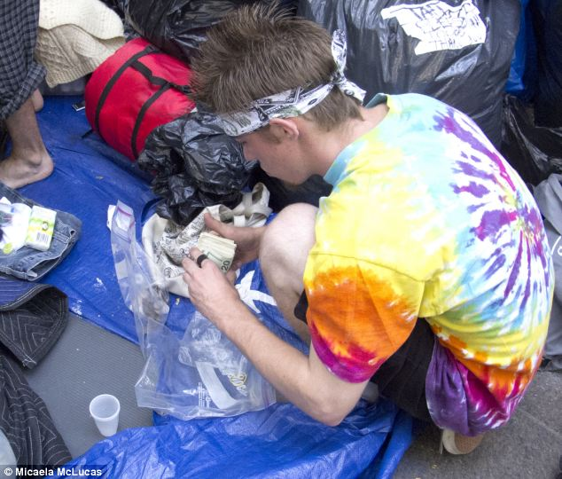 Financial inequality? One of the young men camping out flashes a wad of cash