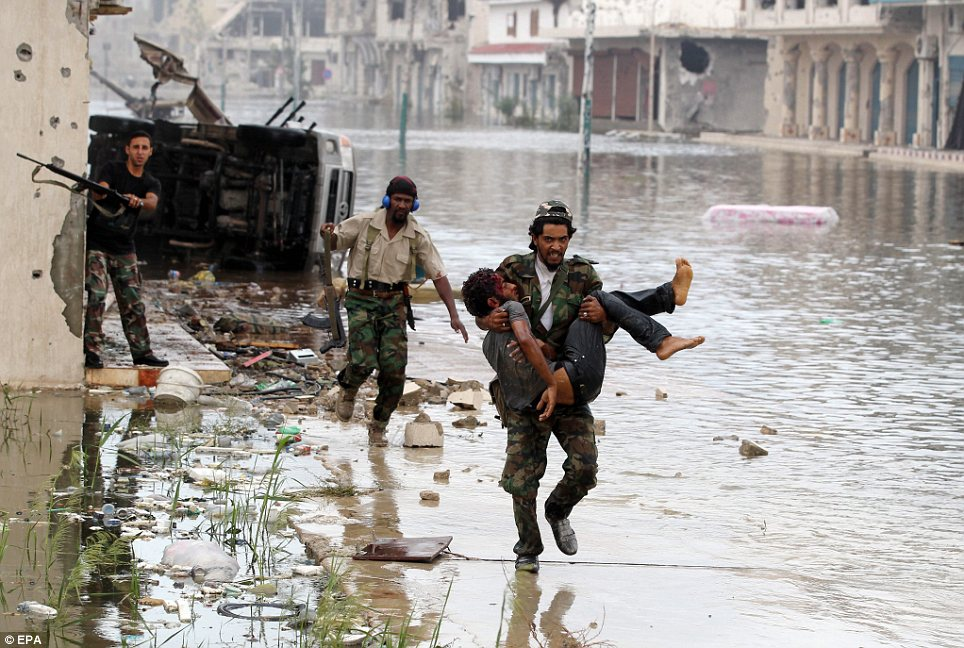 Combat: A Libyan rebel carries the body of a dead comrade as the war between pro- and anti-Gaddafi forces rumbles on