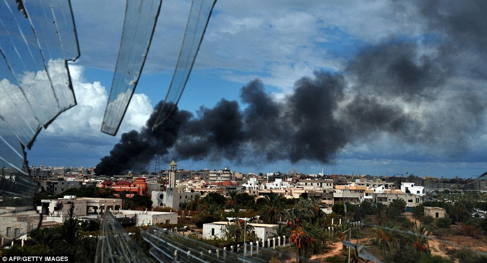 Shattered skyline: Smoke billows over Sirte as the rebels assault continued to pound the centre of the city