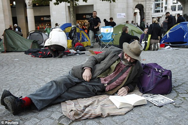 Laid-back approach: A demonstrator reads a book near tents belonging to other demonstrators during the London protest