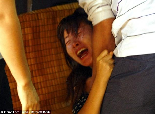 La desesperación: la madre de Yue Yue reacciona después de descubrir el niño fue atropellado mientras ella estaba en un mercado cercano