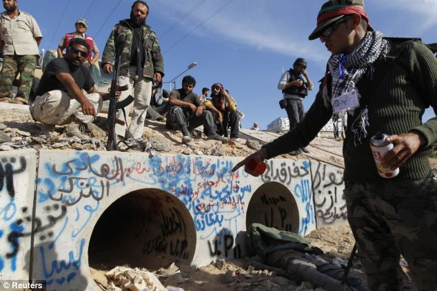 Already a monument: As celebrations continued, more and more graffiti appeared at the entrance to the drain where the leader was eventually found