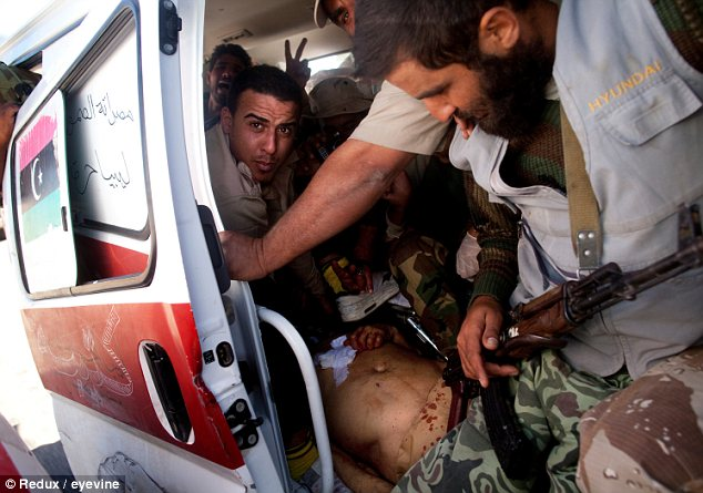 Bundled: An ambulance carries Gaddafi's body from Sirte to Misrata