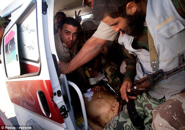 Bundled: An ambulance carries Gaddafi's body from Sirte to Misrata
