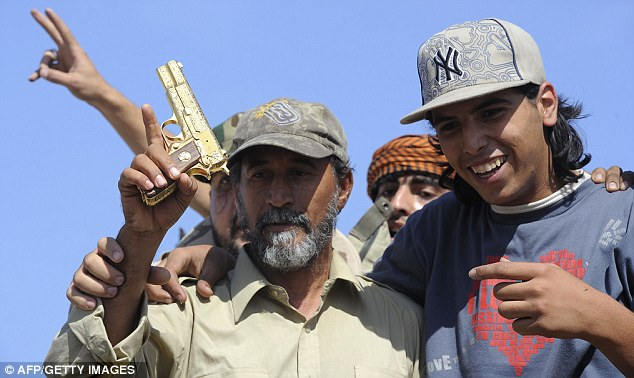 Celebration: Mohammed al-Bibi, seen here in a Yankees hat, points to a comrade holding Gaddafi's golden gun. Al-Bibi is the one who found the despot in his final hiding place and duly claimed the war souvenir