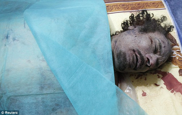 The body of Gaddafi is covered with a blue plastic sheet at a house in Misrata. He is due to be buried at a secret funeral within the next 24 hours