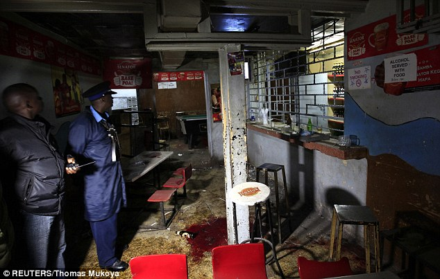 Wreckage: Police inspect the scene following a grenade attack on Mwaura's bar in the early hours of this morning