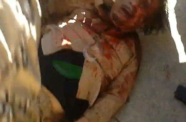Bloodied body of Qaddafi.