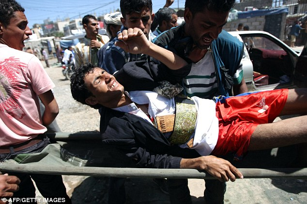 Stretcher bearers: Protesters carry an injured colleague to hospital