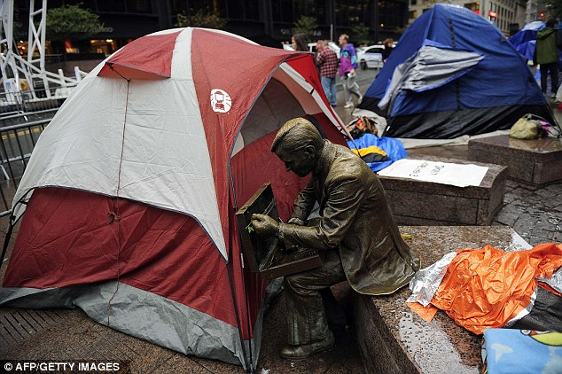 """Camping: carpas se han levantado en torno a """"Double Check"""", un hombre de negocios de bronce sentado en un banco, como la lluvia cae"""