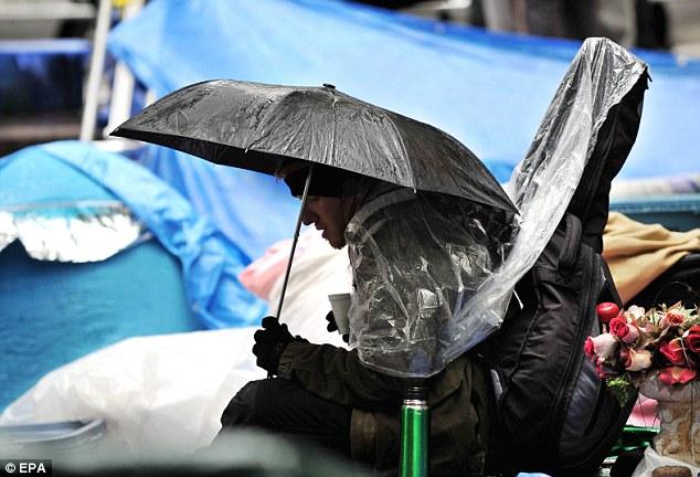 Húmedo: Un hombre se sienta bajo un paraguas en el Zuccotti Park en el campamento Ocupar Wall Street en Nueva York