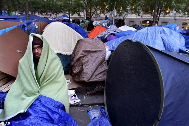 Frío: Christopher Guerra, de San Francisco, California, está envuelto en una manta para mantener el calor mientras se participa en la protesta Ocupar Wall Street en el campamento de Zuccotti Park el viernes en Nueva York