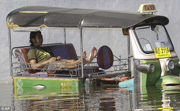 No fares: A submerged taxi is left stranded by the deluge