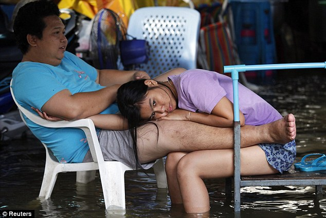Sitting it out: A couple can only wait for the waters to recede at a flooded market in Bangkok