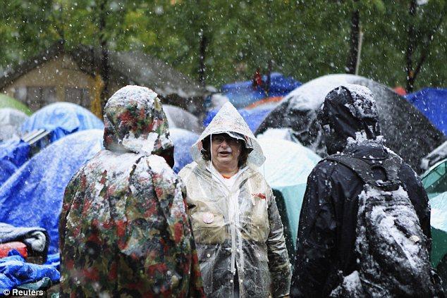 Pow-wow: Como la nieve cae a su alrededor, los miembros de la Ocupar la calle Muro de movimiento de discutir el tiempo mientras está de pie en el Zuccotti Park