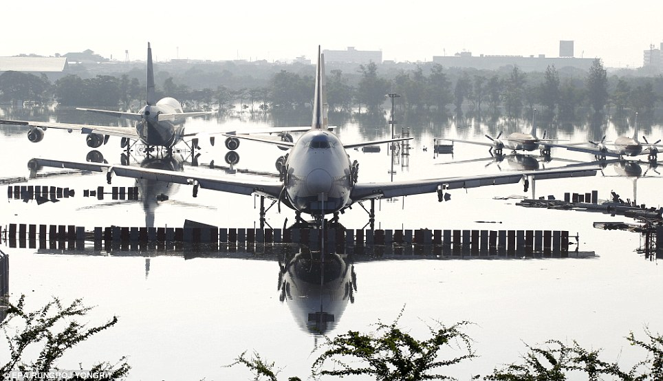 Grounded: Several more jetliners sit on the airport's flooded runway, where authorities have been powerless to prevent advancing waters pouring across the airport